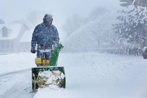 A picture of a man doing snow removal on a sidewalk with a snowblower in Grande Prairie.