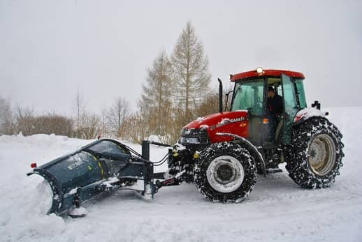 A picture of a red tractor with a blade doing snow removal services in Grande Prairie.